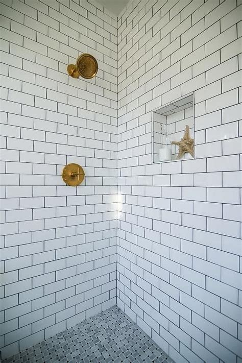 Stunning shower features walls clad in white subway tiles
